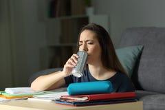 Estudiante cansado que bebe una bebida de la energía imagen de archivo libre de regalías
