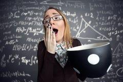 Estudiante cansado que bosteza con la taza de café grande Foto de archivo