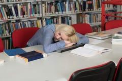 Estudiante cansado que duerme en biblioteca Imágenes de archivo libres de regalías