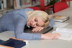 Estudiante cansado que duerme en biblioteca Imagenes de archivo