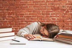 Estudiante cansado que duerme en la biblioteca, espacio libre Fotos de archivo libres de regalías