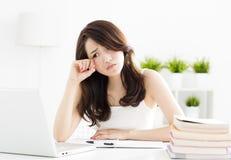Estudiante cansado que estudia con el ordenador portátil Foto de archivo