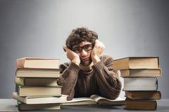 Estudiante cansado que se sienta detrás de los libros Imagen de archivo