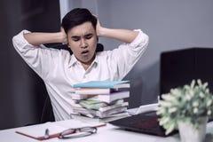 Estudiante cansado que se sienta en la tabla con el libro y el ordenador portátil Fotos de archivo
