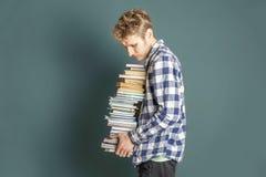 Estudiante casual llevar la pila enorme de libros en el fondo oscuro f fotos de archivo