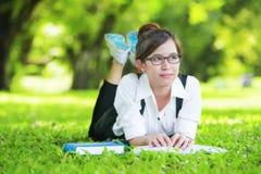 Estudiante casual sonriente que miente en el libro de lectura de la hierba Fotos de archivo libres de regalías