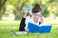 Estudiante casual sonriente que miente en el libro de lectura de la hierba Imagenes de archivo
