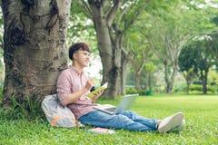 Estudiante casual sonriente que se sienta en la hierba que mira lejos en el campus a Imagen de archivo