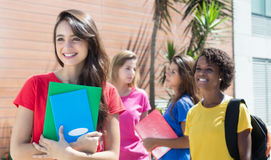 Estudiante caucásico en camisa roja con otros estudiantes internacionales Foto de archivo