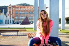 Estudiante caucásico encantador que se sienta en el banco de madera del campus contra el edificio de la universidad Imagenes de archivo