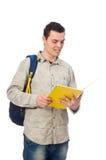 Estudiante caucásico sonriente con la mochila y el libro aislados en whi Foto de archivo