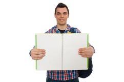 Estudiante caucásico sonriente con la mochila y el libro aislados en whi Foto de archivo libre de regalías