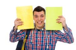 Estudiante caucásico sonriente con la mochila y los libros aislados en wh Imagen de archivo libre de regalías