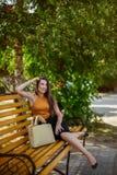 Estudiante, chica joven con un bolso que descansa sobre un banco de parque fotos de archivo