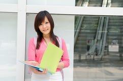 Estudiante chino asiático de la universidad con el fondo del campus Imagen de archivo libre de regalías