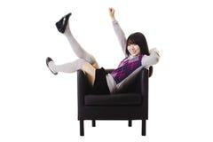 Estudiante chino emocionado en una silla de cuero. Fotografía de archivo
