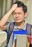 Estudiante chino With Headache del muchacho de la universidad imagen de archivo