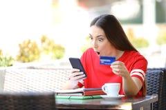 Estudiante chocado que paga en l?nea con la tarjeta de cr?dito en una barra fotos de archivo libres de regalías