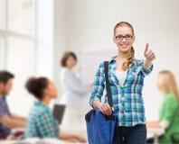Estudiante con el bolso del ordenador portátil que muestra los pulgares para arriba Imagen de archivo libre de regalías