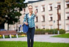 Estudiante con el bolso del ordenador portátil que muestra los pulgares para arriba Imagenes de archivo