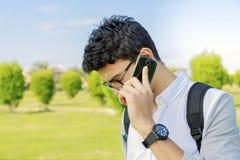Estudiante con el bolso que habla en el teléfono, al aire libre Fotografía de archivo