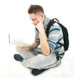Estudiante con el libro de lectura del morral Imagen de archivo libre de regalías