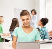 Estudiante con el ordenador portátil en la escuela Imagen de archivo libre de regalías