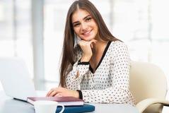 Estudiante con el ordenador portátil en una alta biblioteca escolar Imagen de archivo