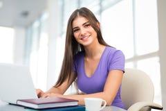 Estudiante con el ordenador portátil en una alta biblioteca escolar Imagen de archivo libre de regalías