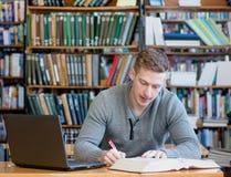 Estudiante con el ordenador portátil que estudia en la biblioteca de universidad Fotos de archivo libres de regalías