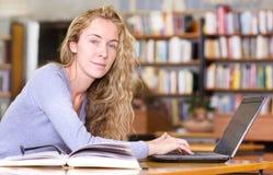 Estudiante con el ordenador portátil que trabaja en biblioteca Fotos de archivo
