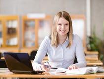 Estudiante con el ordenador portátil que trabaja en biblioteca mirada de la cámara Fotografía de archivo