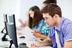 Estudiante con el ordenador que estudia en la escuela Foto de archivo