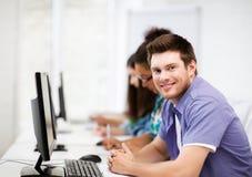 Estudiante con el ordenador que estudia en la escuela Imagen de archivo libre de regalías