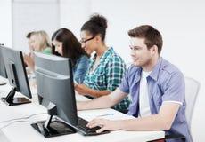 Estudiante con el ordenador que estudia en la escuela Imagen de archivo