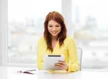Estudiante con el ordenador y el cuaderno de la PC de la tableta Foto de archivo