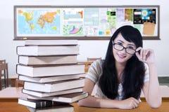 Estudiante con el pelo largo y una pila de libros Imagen de archivo libre de regalías