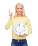 Estudiante con el reloj y el finger de pared para arriba Foto de archivo