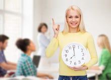 Estudiante con el reloj y el finger de pared para arriba Imagenes de archivo