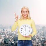 Estudiante con el reloj y el finger de pared para arriba Fotos de archivo libres de regalías