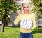 Estudiante con el reloj y el finger de pared para arriba Fotografía de archivo libre de regalías