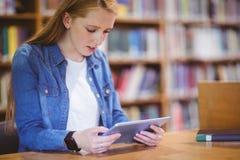 Estudiante con el smartwatch usando la tableta en biblioteca Fotos de archivo