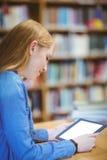 Estudiante con el smartwatch usando la tableta en biblioteca Imágenes de archivo libres de regalías