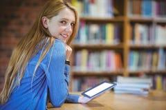 Estudiante con el smartwatch usando la tableta en biblioteca Imagen de archivo