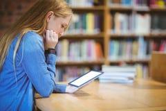 Estudiante con el smartwatch usando la tableta en biblioteca Fotos de archivo libres de regalías
