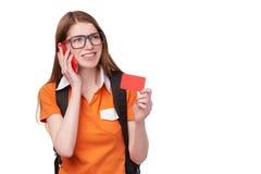 Estudiante con el teléfono celular que sostiene la tarjeta de crédito Fotografía de archivo libre de regalías