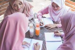 Estudiante con la bufanda principal que estudia junto Imagen de archivo