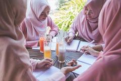 Estudiante con la bufanda principal que estudia junto Fotos de archivo