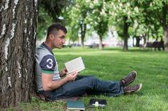 Estudiante con la lectura del monopatín y de la mochila Fotos de archivo libres de regalías
