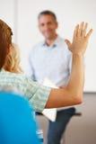 Estudiante con la mano para arriba en clase Fotografía de archivo
